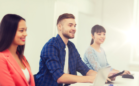 happy creative team or students working at office