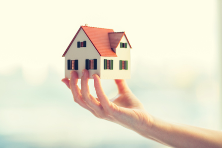 close up of hands holding house or home model Stock Photo