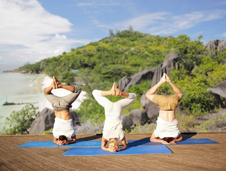people making yoga headstand over tropical beach Stock Photo - 76687958