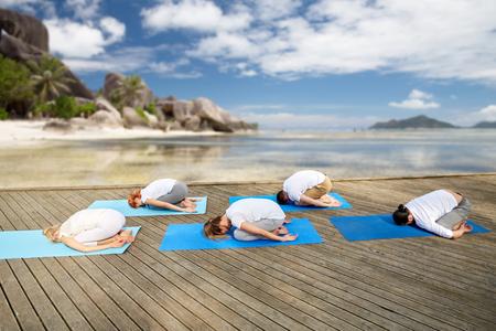 group of people making yoga exercises over beach Banco de Imagens