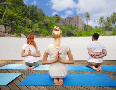 reverse: group of people making yoga exercises over beach Stock Photo
