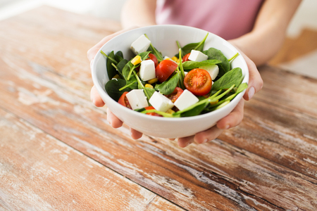 hands holding bowl of vegetable salad over table Stock Photo