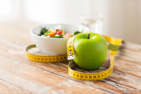 Nahaufnahme von grünem Apfel und Maßband Standard-Bild - 76606872