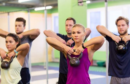 group of people with kettlebells exercising in gym