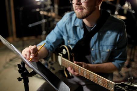 el hombre con la escritura guitarra para el libro de música en el estudio photo