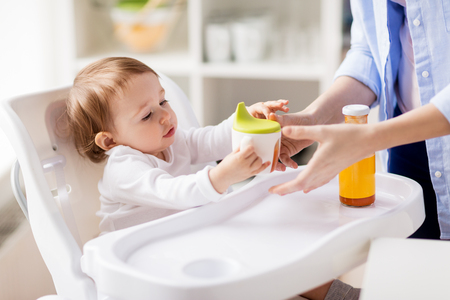 mother giving spout cup with juice to baby at home Imagens - 76688094