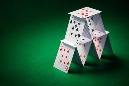 Huis van speelkaarten op groene tafelkleed