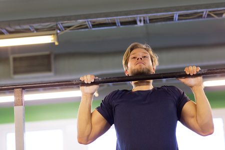 man exercising on bar and doing pull-ups in gym Stock Photo