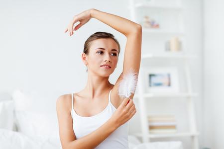 Vrouw met veer die haar oksel aanraakt