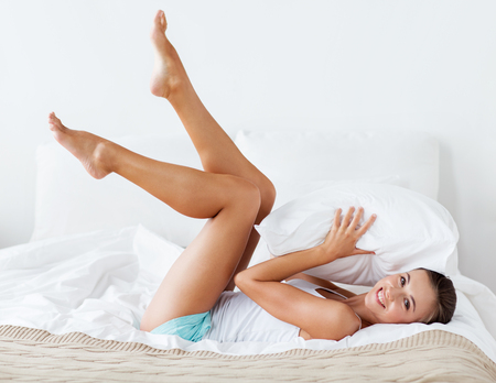 woman lying: happy young woman with pillow lying in bed at home