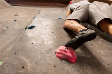 foot of man exercising at indoor climbing gym