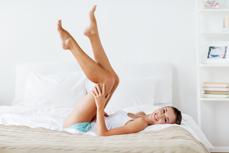 happy woman lying on bed and touching legs at home