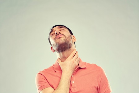 man touching neck and suffering from throat pain Stock Photo