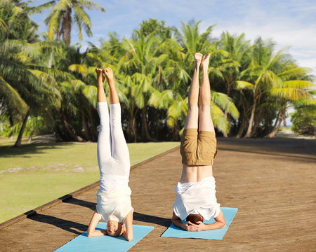 fitness, sport, yoga, people and healthy lifestyle concept - couple making headstand pose on mat over natural exotic background with palm trees Stock Photo - 76875951