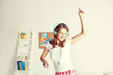 nightwear: happy woman in headphones ihaving fun at home