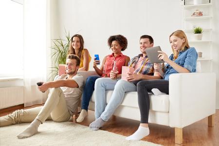 Amis avec gadgets et de la bière en regardant la télévision à la maison Banque d'images - 76887008