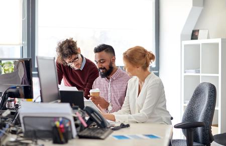 bedrijfsleven, opstarten en mensen concept - internationaal creatief team met papieren en tablet pc computer in kantoor Stockfoto
