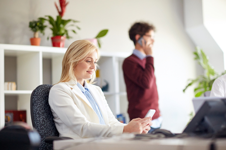 multiple: business corporate, technology and people concept - happy businesswoman texting on smartphones at office Stock Photo