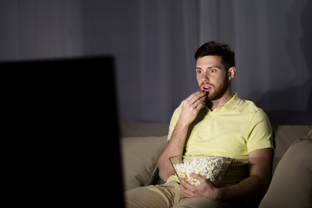 entertainment concept: people, mass media, television and entertainment concept - young man watching tv and eating popcorn at night at home