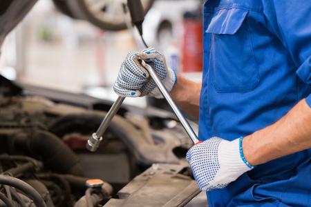 Auto-Service, Reparatur, Wartung und Menschen Konzept - Automechaniker Mann mit Schraubenschlüssel und Lampe arbeiten in der Werkstatt Standard-Bild - 76882015