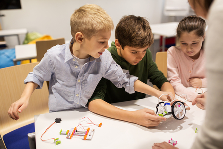 multiple: education, children, technology, science and people concept - group of happy kids building robots at robotics school lesson
