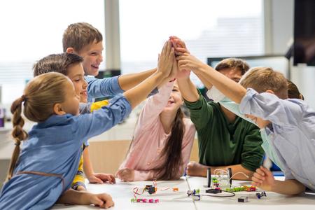 교육, 어린이, 기술, 과학 및 사람들이 개념 - 로봇을 구축 하 고 로봇 학교에서 높은 5 제스처를 만드는 행복 한 아이들의 그룹 스톡 콘텐츠