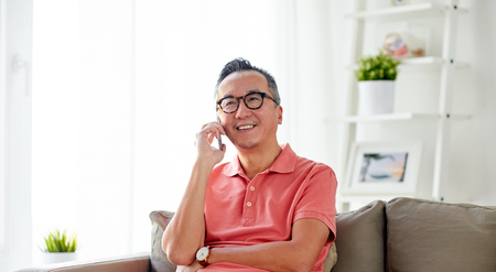 technology, people, lifestyle and communication concept - happy man sitting on sofa calling on smartphone at home Imagens