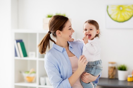 family, teething, motherhood and people concept- happy mother and little baby girl at home kitchen Stock Photo