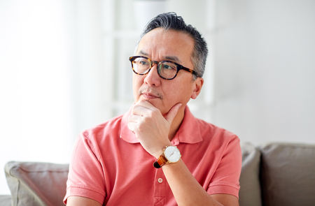 people concept - asian man thinking at home Stock Photo - 76882494
