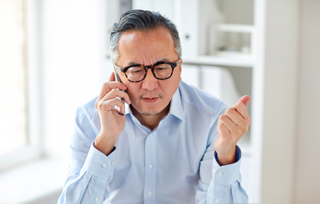 business, people, communication and technology concept - serious asian businessman calling on smartphone in office Banque d'images