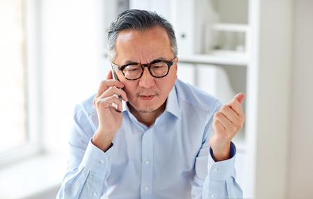 Geschäft, Leute, Kommunikation und Technologiekonzept - ernster asiatischer Geschäftsmann, der um Smartphone im Büro ersucht Standard-Bild