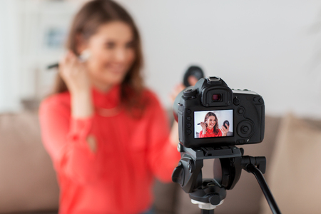 powder room: blogging, technology, videoblog, makeup and people concept - happy smiling woman or beauty blogger with bronzer, brush and camera recording tutorial video at home