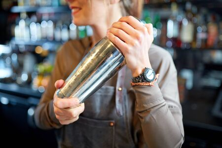 alcohol drinks, people and luxury concept - close up of smiling woman bartender with steel shaker preparing cocktail at bar