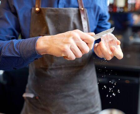人と職業の概念 - バーテンダーでナイフでアイス キューブを研削バー