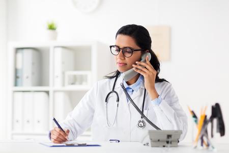 geneeskunde, mensen en gezondheidszorgconcept - gelukkige vrouwelijke arts met documenten en klembord die telefoon uitnodigen bij het ziekenhuis Stockfoto