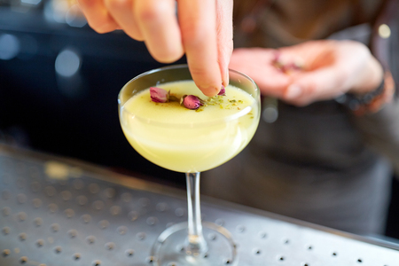 adding: alcohol drinks, people and luxury concept - bartender hand decorating cocktail in glass with dried flowers at bar Stock Photo