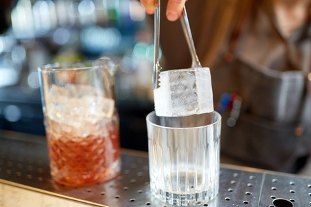 alcohol drinks, people and luxury concept - bartender with tongs adding ice cube into glass and preparing cocktail at bar counter