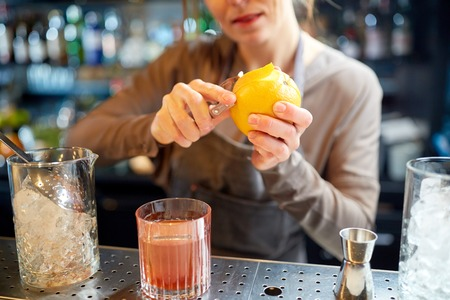 alcohol drinks, people and luxury concept - woman bartender with glass and peeler removing peel from orange and preparing cocktail at bar