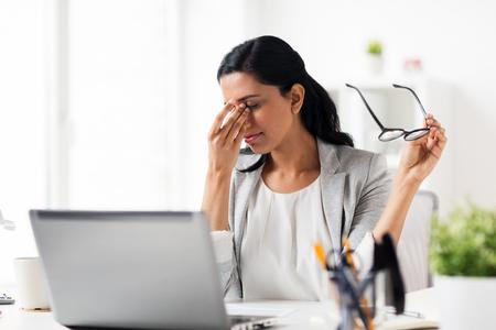 biznes, przemęczenia, termin, wizja i ludzie pojęcie - zmęczony bizneswoman w szkłach pracuje przy biurem i naciera oczy