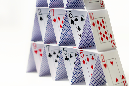 house of playing cards over white background Imagens - 76887088