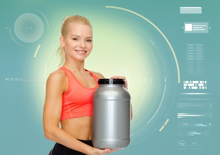 smiling sporty woman with sports nutrition jar
