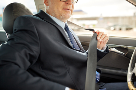 senior businessman fastening car seat belt