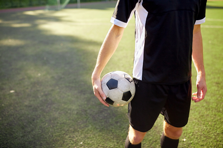 sport, football training and people concept - close up of soccer player with ball on field