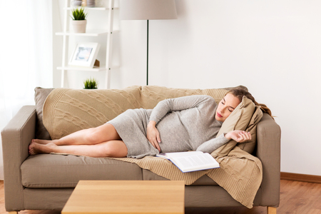 pregnancy, rest, people and expectation concept - happy pregnant woman sleeping on sofa at home photo