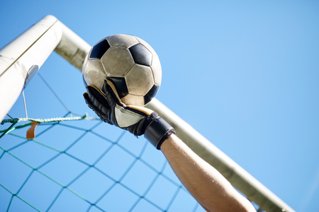 sport and people - soccer player or goalkeeper hand catching ball at football goal over blue sky Stock Photo