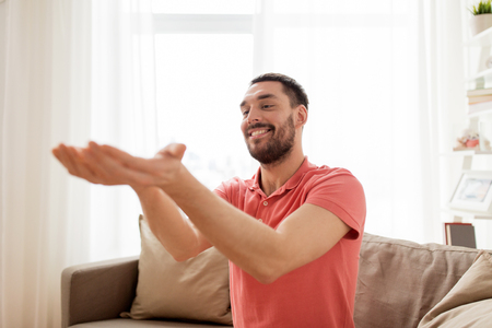 virtual reality, entertainment and people concept - happy man holding something imaginary on palms at home