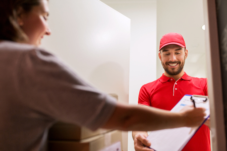 addressee: delivery, mail, people and shipping concept - happy man with clipboard delivering parcel boxes to customer signing form at home Stock Photo