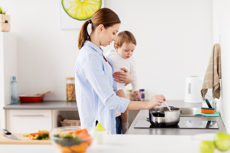 family, food, healthy eating and people concept - happy mother and little baby girl cooking dinner together at home kitchen