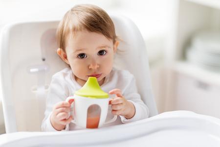 幼年期および人々 コンセプト - 小さな赤ちゃんから飲んで噴出自宅ハイチェアに座ってカップ