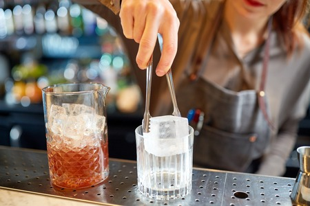 alcohol drinks, people and luxury concept - woman bartender with tongs adding ice cube into glass and preparing cocktail at bar counter